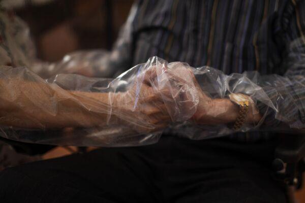 Dolores Reyes Fernandez, 61 lat, po raz pierwszy od 4 miesięcy trzyma ręce ojca José Reyesa Lozano w domu opieki w Barcelonie  - Sputnik Polska