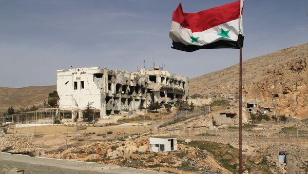Syryjska flaga na tle zniszczonego domu w syryjskim mieście Maalula - Sputnik Polska