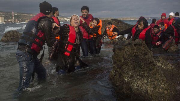 Bliskowschodni uchodźcy wysiadający z łodzi na wybrzeżu greckiej wyspy Lesbos - Sputnik Polska