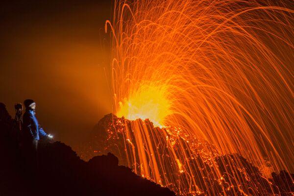 Mężczyzna patrzy na erupcję wulkanu Piton de la Fournaise na wyspie Reunion na oceanie Indyjskim - Sputnik Polska