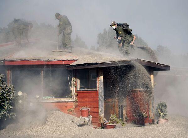 Policjanci czyszczą dom, pokruty popiołem z wulkanu Calbuco w Chile - Sputnik Polska