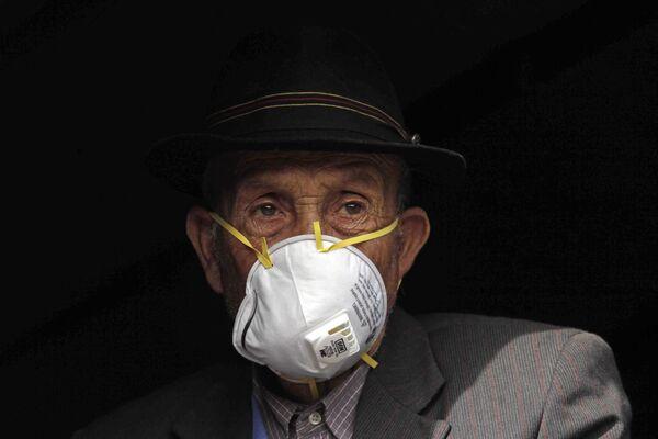 Mężczyzna w masce od pyłu wulkanicznego czeka wewnątrz ciężarówki wojskowej podczas ewakuacji - Sputnik Polska