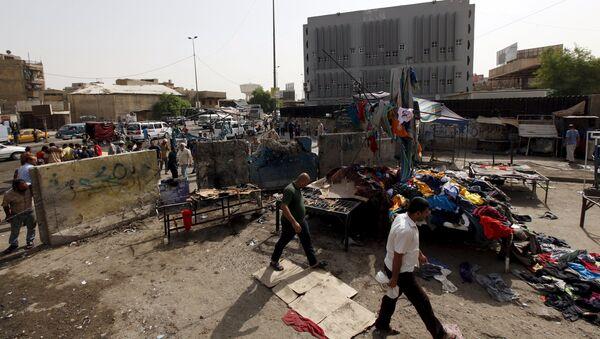 Men walk past the site of a suicide bomb attack in Baghdad, Iraq - Sputnik Polska