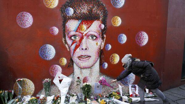 Fanka Davida Bowie składa kwiaty pod portretem-graffiti artysty w Londynie - Sputnik Polska