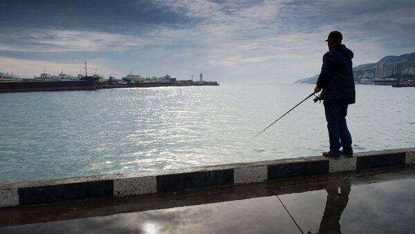 Mężczyzna łowi rybę na Krymie - Sputnik Polska