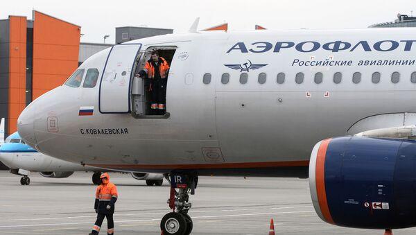 Pracownicy lądowych służb technicznych w pobliżu samolotu Airbus A320 linii lotniczych Aerofłot na międzynarodowym lotnisku Szeremietiewo - Sputnik Polska