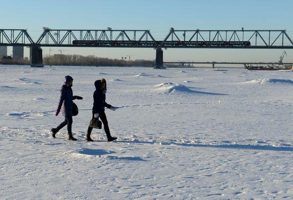 Mieszkańcy Nowosybirska spacerujący po zamarzniętej rzece Ob w pobliżu mostu kolejowego będącego częścią Kolei Transsyberyjskiej. - Sputnik Polska