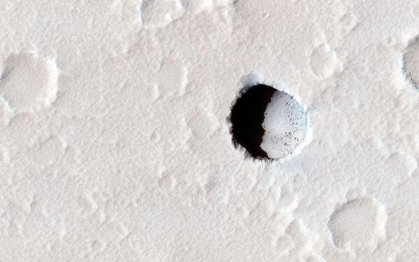 Głęboki krater na południowo-wschodnim stoku marsjańskiej góry Elysium Mons - Sputnik Polska