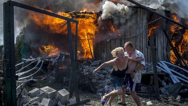 Mieszkańcy uciekają od pożaru w domu zniszczonym przez atak Sił Zbrojnych Ukrainy na wsi Ługanskaja - Sputnik Polska