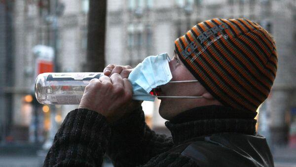 Mieszkaniec Kijowa w masce ochronnej pije wódkę - Sputnik Polska