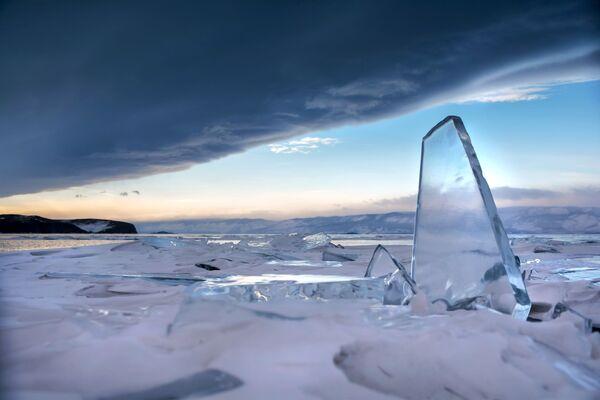 Zwały lodu na tle chmur burzowych nad jeziorem Bajkał. - Sputnik Polska