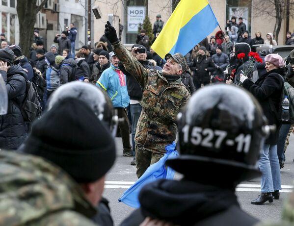 Uczestnik akcji protestacyjnej rzuca kamień w stronę jednego z rosyjskich banków w Kijowie - Sputnik Polska