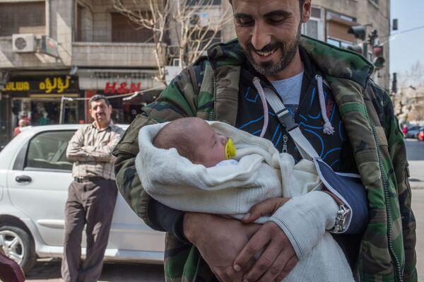 Mężczyzna z dzieckiem na ulicy Damaszku - Sputnik Polska