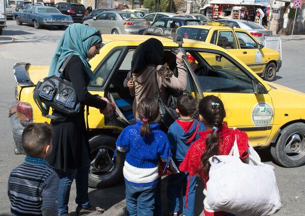 Kobiety z dziećmi wsiadają do taksówki na ulicy Damaszku - Sputnik Polska