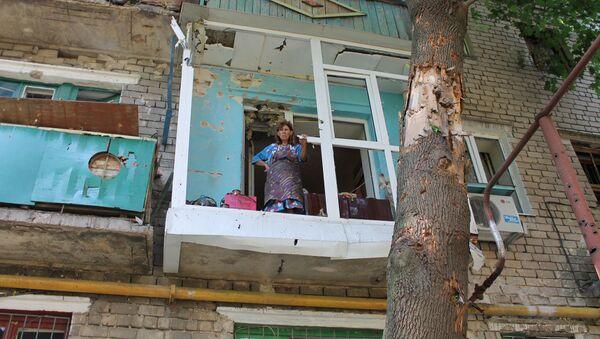 Kobieta na balkonie swojego mieszkania, zniszczonego podczas ostrzału przez ukraińską armię - Sputnik Polska