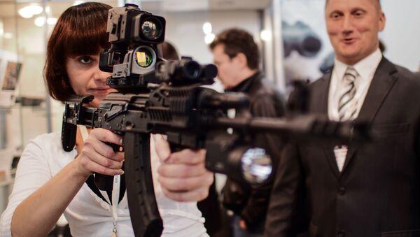 Dziewczyna trzyma karabin Kałasznikowa AK-103 - Sputnik Polska