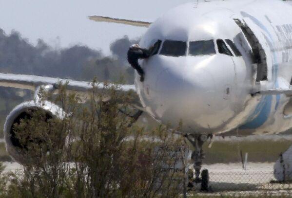 Mężczyzna wychodzi przez rozbite okno samolotu linii Egyptair na lotnisku w Larnace - Sputnik Polska