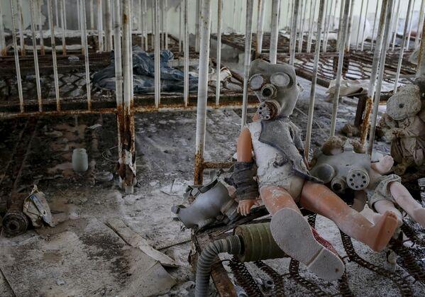 Dziecięca lalka w masce przeciwgazowej w ruinach Prypeci - Sputnik Polska
