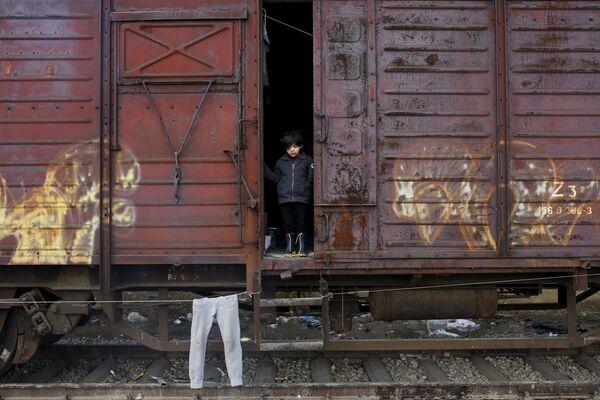 Dziecko wyglądające z wagonu w zaimprowizowanym obozie dla imigrantów na granicy  Grecji i Macedonii - Sputnik Polska