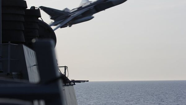 An undated US Navy picture shows what appears to be a Russian Sukhoi SU-24 attack aircraft making a very low pass close to the U.S. guided missile destroyer USS Donald Cook in the Baltic Sea. - Sputnik Polska