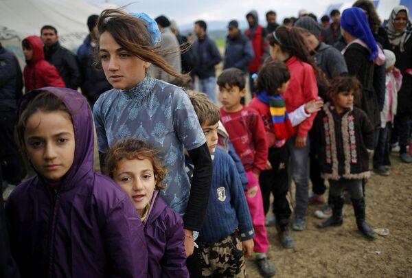Uchodźcy stoją w kolejce po herbatę w obozie w greckiej miejscowości Idomeni - Sputnik Polska