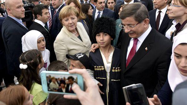 Kanclerz Niemiec Angela Merkel i turecki premier Ahmet Davutoglu odwiedzili jeden z obozów dla uchodźców w prowincji Gaziantep na południowym wschodzie Turcji - Sputnik Polska
