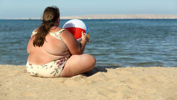 Overweight woman sitting with ball on beach near sea - Sputnik Polska