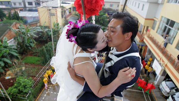 Para młoda w trakcie ceremonii ślubnej wisi między piętrami budynku w Chinach. - Sputnik Polska