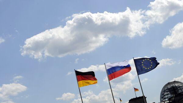 Rosyjska flaga pomiędzy flagą Niemiec i UE, w tle Reichstag (Berlin) - Sputnik Polska