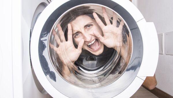 Kobieta patrzy przez drzwi pralki - Sputnik Polska