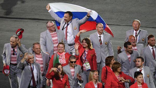 Przedstawiciel białoruskiej delegacjiAndriej Fomoczkin z flagą Rosji podczas parady atletów i członków reprezentacji narodowych na ceremonii otwarcia XV letnich Igrzysk Paraolimpijskich 2016 w Rio de Janeiro - Sputnik Polska