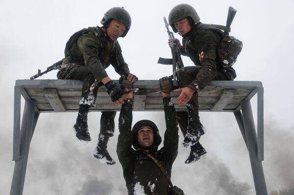 10-kilometrowy marsz i specjalny pas szturmowy z wieloma przeszkodami żołnierze przechodzą pomagając sobie wzajemnie. - Sputnik Polska