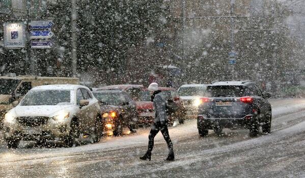 Kobieta przechodzi przez ulicę podczas śnieżycy w Krasnojarsku - Sputnik Polska