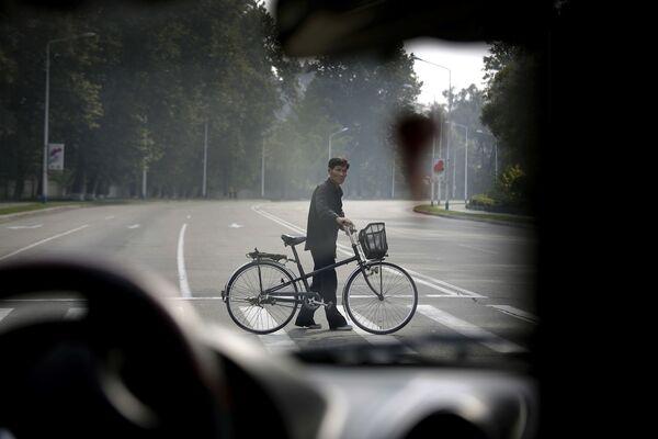 Mężczyzna z rowerem przechodzi drogę, Pjongjang - Sputnik Polska
