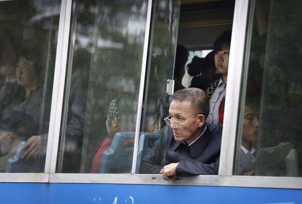 Pasażerowie tramwaju patrzą przez okno, Pjongjang - Sputnik Polska
