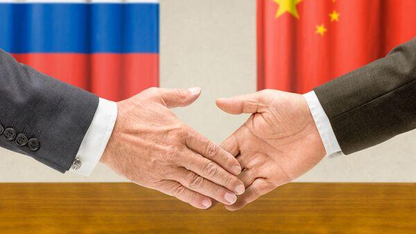 Dłonie na tle flag Rosji i Chin - Sputnik Polska