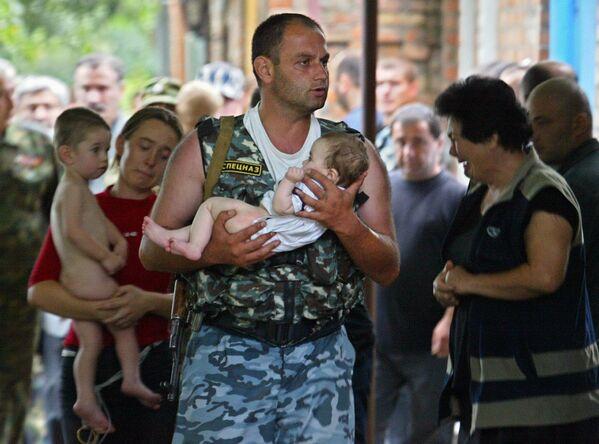 Komandos niesie dziecka po wyzwoleniu szkoły w Biesłanie od terrorystów - Sputnik Polska