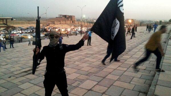 Członek organizacji terrorystycznej PI z flagą na ulicy Mosulu w Iraku - Sputnik Polska