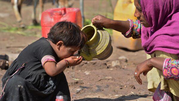 Пакистанская женщина поит своего ребенка водой из кувшина - Sputnik Polska