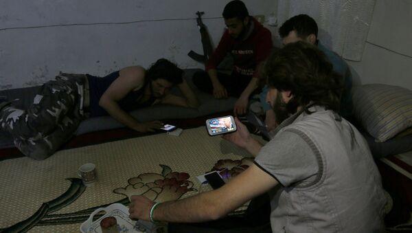 Islamiści z grupy Harakat Nour al-Din al-Zenki oglądają na smartfonie wiadomości po ogłoszeniu wyniku wyborów prezydenckich w USA, Aleppo, 9 listopada 2016 - Sputnik Polska