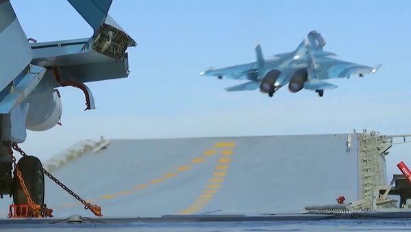 """Myśliwiec Su-33 ląduje na pokładzie ciężkiego krążownika lotniskowego """"Admirał Floty Związku Radzieckiego Kuzniecow"""" u brzegów Syrii - Sputnik Polska"""