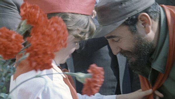 Pionera soviética cuelga un pañuelo rojo (símbolo de los pioneros) en el cuello de Fidel Castro. - Sputnik Polska