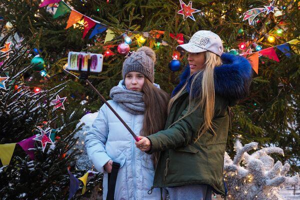 Mama z córka robią selfie przy choince noworocznej na Placu Czerwonym w Moskwie - Sputnik Polska