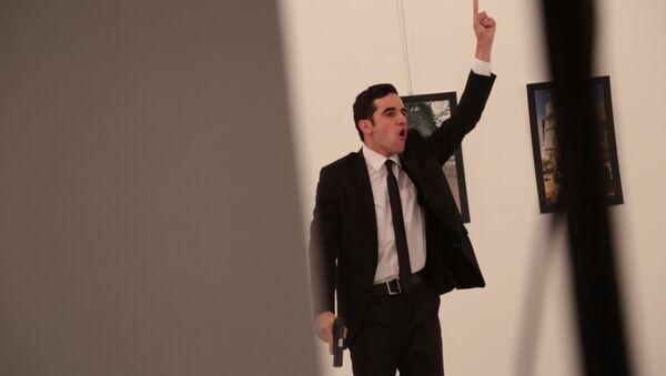 Uzbrojony mężczyzna obok ciała rosyjskiego ambasadora w Turcji Andrieja Karłowa w galerii w Ankarze - Sputnik Polska
