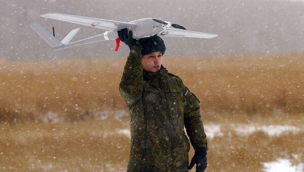 Elew trzyma w ręku dron Orłan-10 na poligonie w obwodzie moskiewskim  - Sputnik Polska