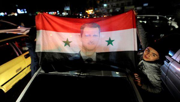 Flaga Syrii z wizerunkiem prezydenta Baszara al-Asada - Sputnik Polska