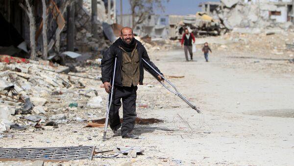 Mężczyzna w zniszczonej dzielnicy Aleppo - Sputnik Polska