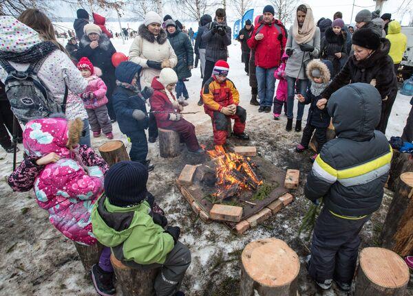 Mieszkańcy Karelii grzeją się przy ognisku podczas Międzynarodowego Zimowego Festiwalu Hiperborea w Karelii. - Sputnik Polska