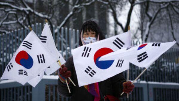 Kobieta trzyma flagi Korei Południowej podczas protestu przed ambasadą Korei Północnej w Berlinie - Sputnik Polska