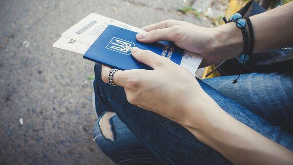 Dziewczynka z ukraińskim paszportem i biletami w ręku - Sputnik Polska